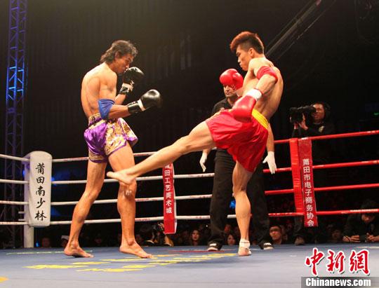 泰国拳王蓝桑坤(左)与中国19岁小将许振光在比赛中.林剑冰摄-世图片
